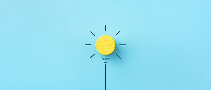 Inspiration, Innovation concept, yellow wooden cube on blue background, copy space