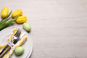 Festive Easter table setting with eggs and flowers on light wooden background, flat lay. Space for text