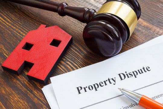Property dispute documents, small home and gavel.