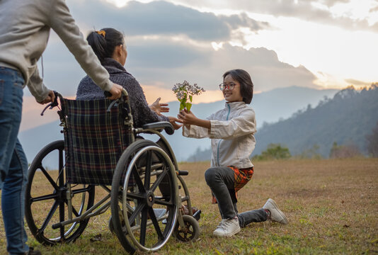 disabled handicapped woman sitting on her wheelchair with her daughter and care helper at sunset