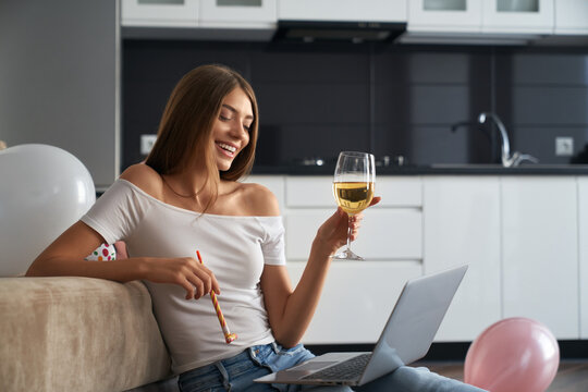 Birthday woman with glass of wine having video call at home