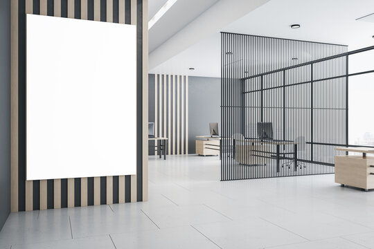 Blank white poster on wooden wall in modern open space office with airy partition, wooden tables, and big window. Mock up