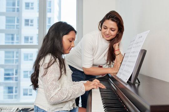Happy proud smiling young Indian woman looking at her teenage daughter playing piano at home