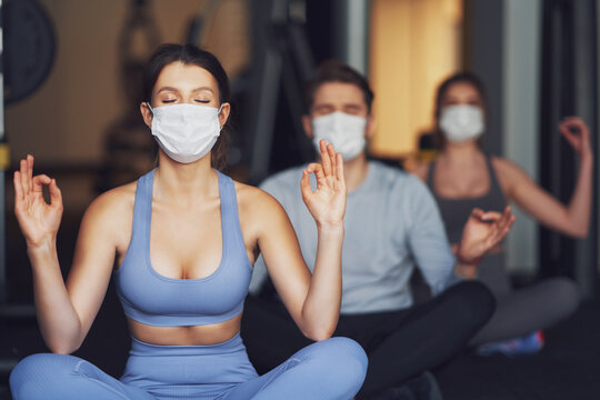 Group of people wearing masks working out in a gym