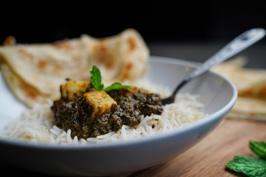 Palak Paneer or Saag Paneer-Indian cottage cheese with Spinach served with rice and roti, selective focus