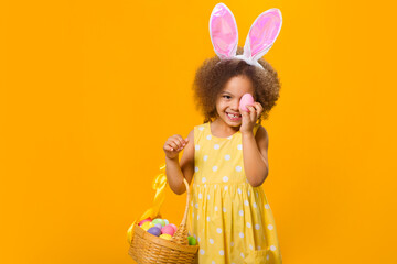 A cheerful african girl with rabbit ears on her head with a basket of colored eggs in her hands.