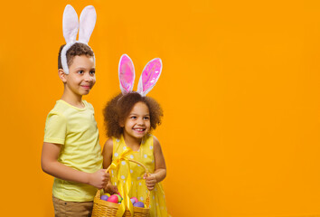 A cheerful girl and boy with rabbit ears on her head with a basket of colored eggs in her hands looks away.