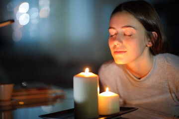 Fototapeta Woman smelling a lighted candle in the night