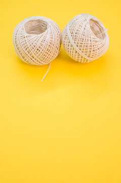 Vertical shot of two white balls of twine isolated on a yellow background