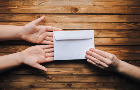 White small envelope (letter) in the hands of two people on brown wooden background. The concept of writing, online donation, email. The Internet.