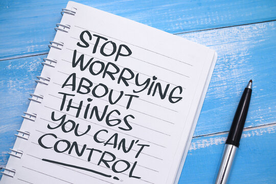 Stop worrying about things you cant control, text words typography written on paper against wooden background, life and business motivational inspirational