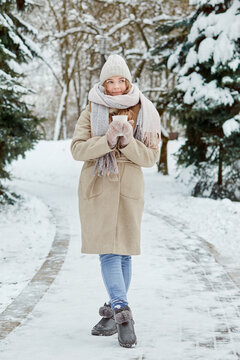 A full-length young woman with a cup of coffee in a winter park. Winter coat and knitted hat. Lots of white snow.