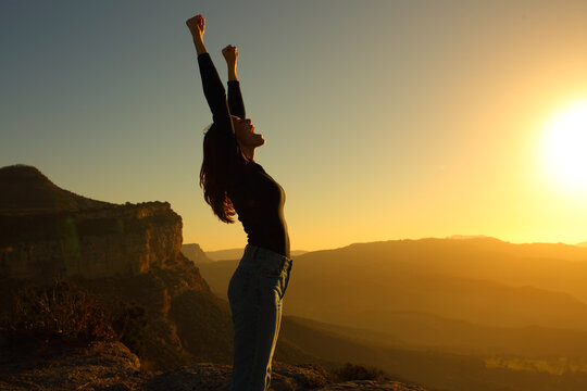 Profile of a woman screaming raising arms celebrating sunset