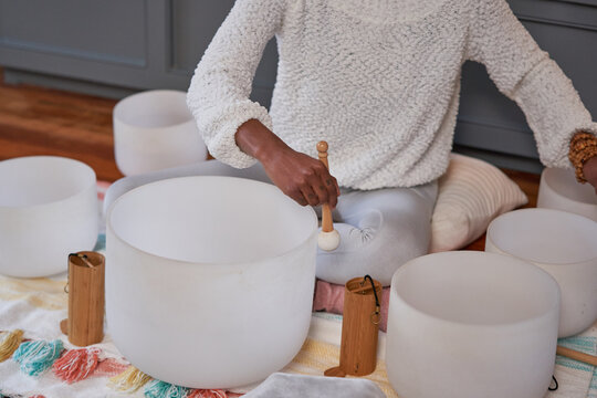 Black woman playing sound bath drums for mediation