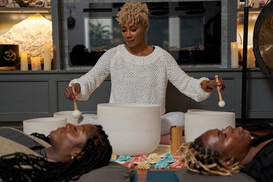 Black women having peaceful mediation laying down, self care retreat