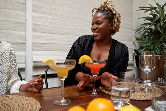 Cheerful Black friends chatting and having drinks at home staycation
