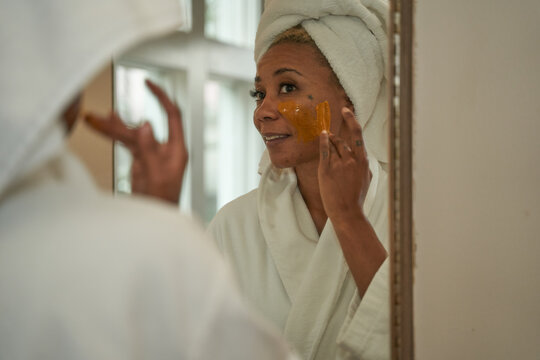 Black woman puts on DIY facial mask, skincare self care