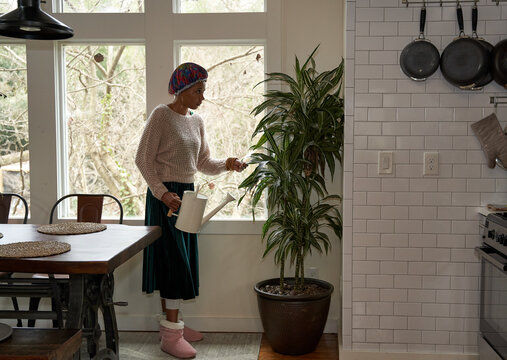 Black woman watering her plants at home