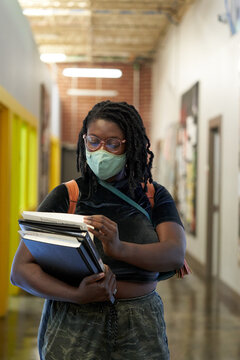 Black female college student walking down hallway with school books, wearing a face mask
