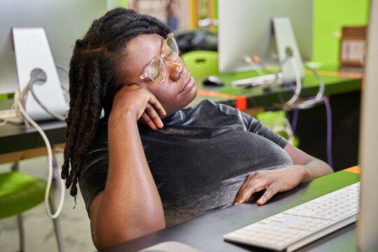 Black female college student tired and exhausted in computer lab