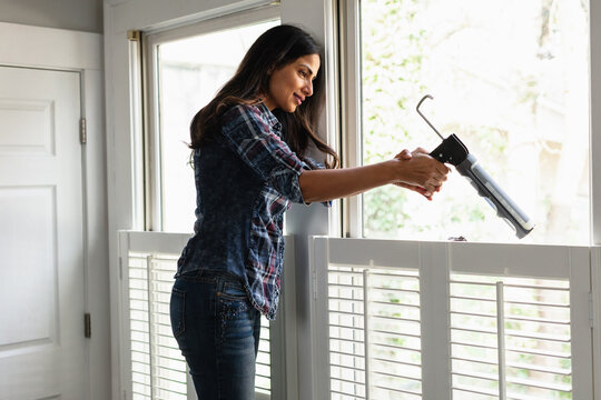 Indian woman weather sealing, caulking windows for winter, DIY home improvement, winterized, energy efficiency