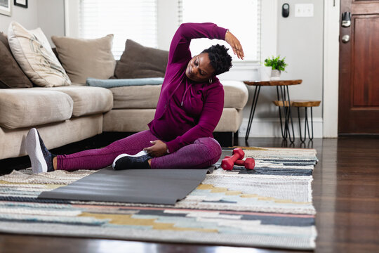 Black woman stretching at home in family room