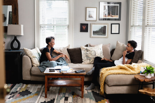Black mother son having talk in family room, on couch, middle class home