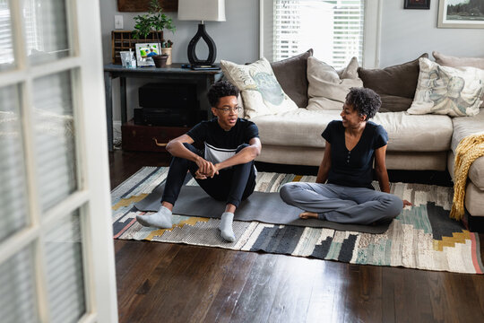 Teen son and mother talking in family room on yoga mat
