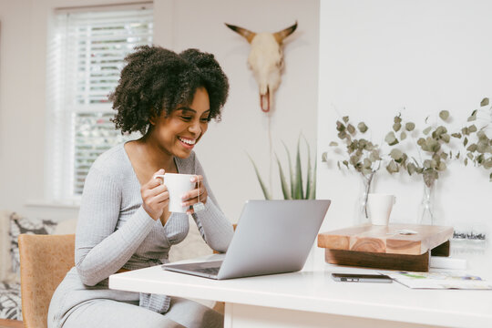 Woman working from home, drinks morning coffee