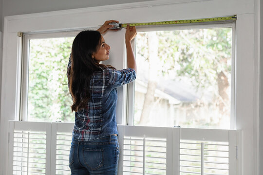 Indian woman uses tape measure tool on home window, measurements for do-it-yourself project