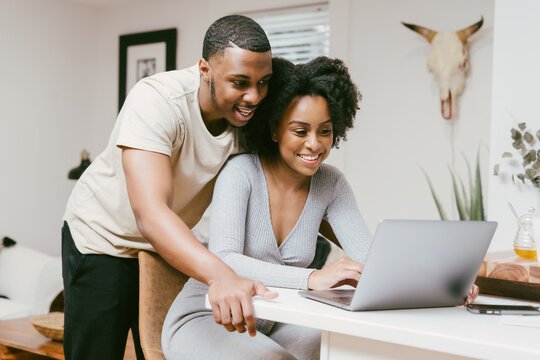Smiling couple, boyfriend looks over girlfriend shoulder while she works on laptop, intimate moment