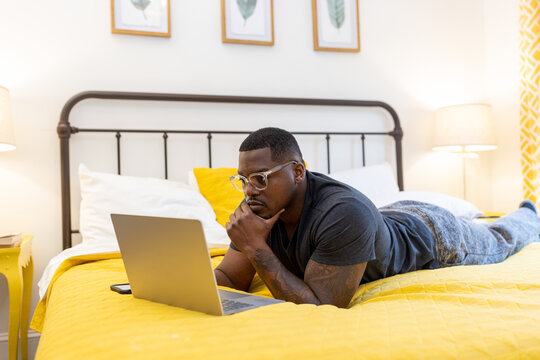 Black man working from home on laptop in bed