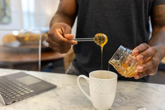 Black man adds honey sweetener to tea drink