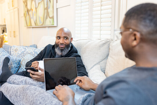 Black gay men have conversations on couch at home