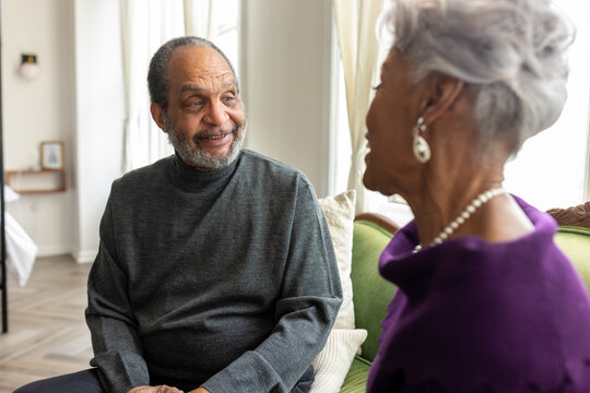 Senior couple connecting and talking at home on couch