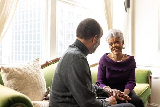 Senior couple sitting at home on sofa, conversations