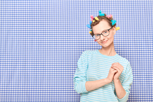 Portrait of happy cute girl with bright colorful hair curlers on head