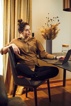 Pregnant woman sitting at home and using laptop.
