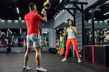 A woman and a man in sportswear look at each other and throw a fitness medicine ball in the gym and do exercises for focus and the whole body. Fitness challenge, a couple of goals Wall mural