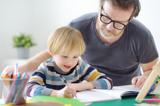 Father helping child do his homework at home. Homeschooling, distance learning, online studying, remote education for kids during quarantine is a problems for parents. Tutor teaching boy with ADHD.