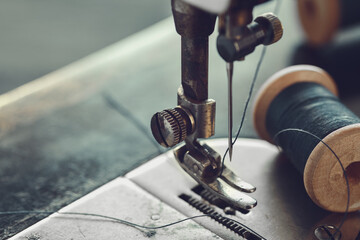 Close up of sewing needle. Spool of thread on working part of antique sewing machine.