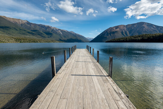 The jetty at Lake Rotoiti, Nelson Lakes National Park, New Zealand. Mountains and sky reflected in the lake.