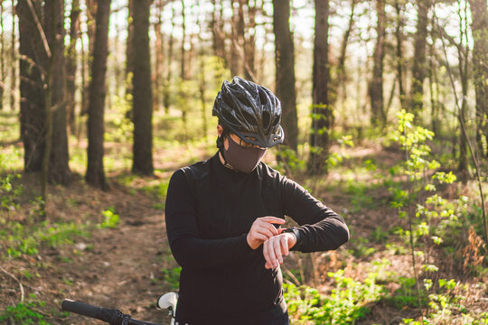 female cyclist wears face mask while cycling on forest path. Feeling short of breath, reducing driving performance. Covid 19. Smog, polluted toxic air, respiratory disease. woman riding mountain bike