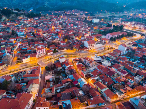 Scenic aerial view of Burdur cityscape with lighted streets and similar brownish tiled roofs on residential buildings in winter twilight, Turkey
