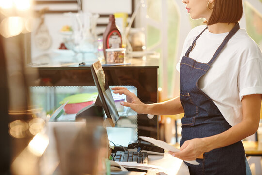 Cropped image of female barista working at coffeeshop and using cash register when accepting payment or entering order detaikls
