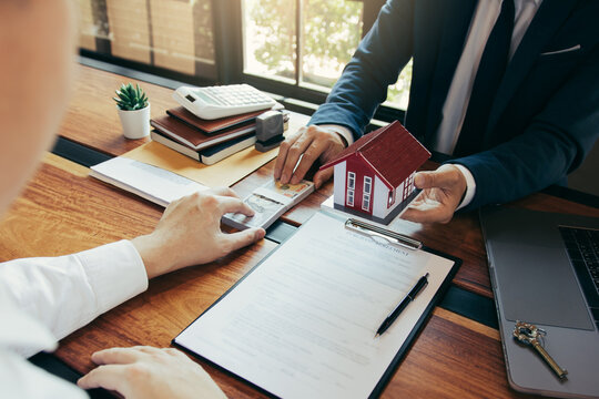 Investors are using st pen on the contract paper about buying a new home while filing cash as a deposit for the agent.
