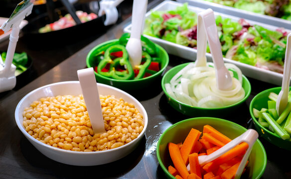 Salad bar buffet at restaurant. Fresh salad bar buffet for lunch or dinner. Healthy food. Beans and orange carrots in white and green bowl on counter. Catering food. Banquet service. Vegetarian food.