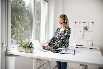 Fototapeta Businesswoman working at ergonomic standing workstation
