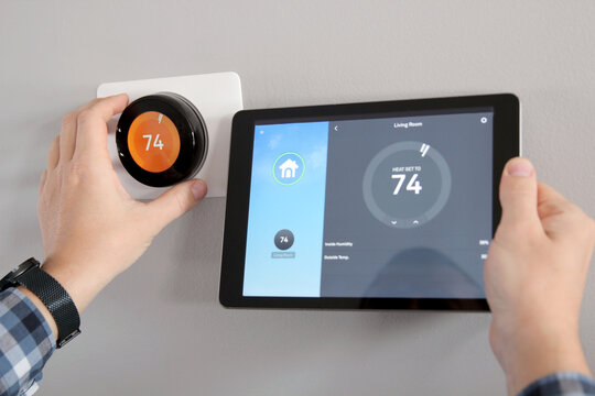 Man is Adjusting a  temperature using a tablet with a smart home app in modern living room