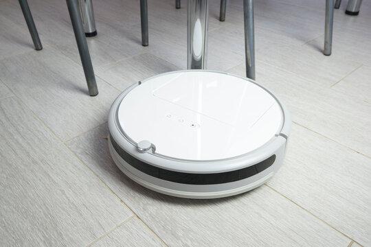 Hoovering floor with modern robotic vacuum cleaner indoors, closeup